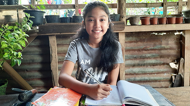 a young Filipina girl sits at a table with books open in front of her