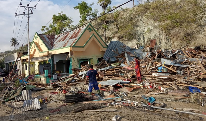 Survivors stand in the debris from the recent Tsunami in Indonesia.