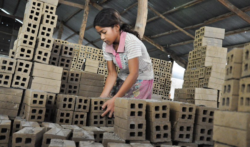 Keota, 11, stacking bricks in the very hot brick factory.