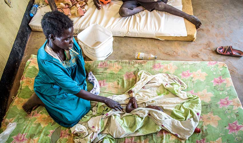 Adut, 28, sits next to her ill one year-old baby, Makuei, who sleeps on a mattress at Warrap State Hospital because there are not enough beds