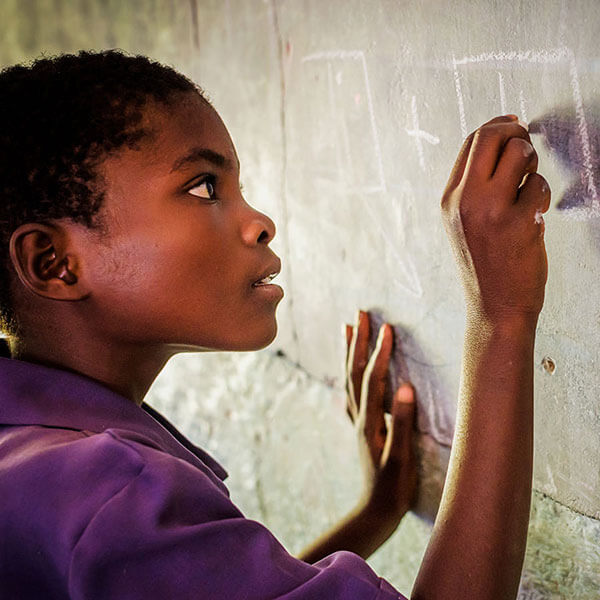 Sponsored child writes on a chalkboard in class