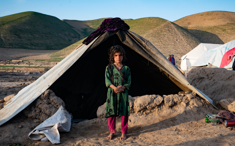 a young Afghan girl stands in front of a tent and looks straight into the camera