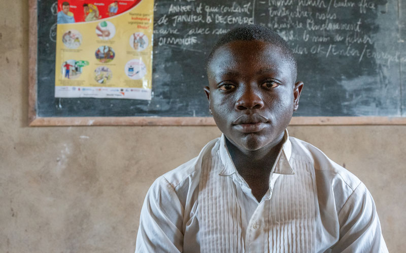A boy from DRC sits in front of chalkboard with writing on it.