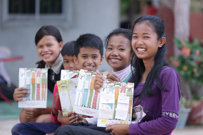 Five children from Cambodia show off colorful Christmas cards.