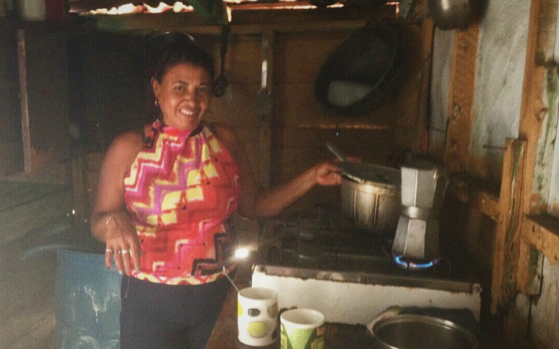 A woman makes coffee in a small kitchen