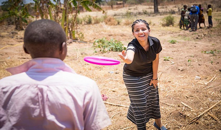 A Canadian woman and Tanzanian boy throw a frisbee back and forth in a Tanzanian village.