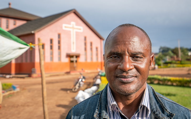 a Congolese man stands in front of a church.