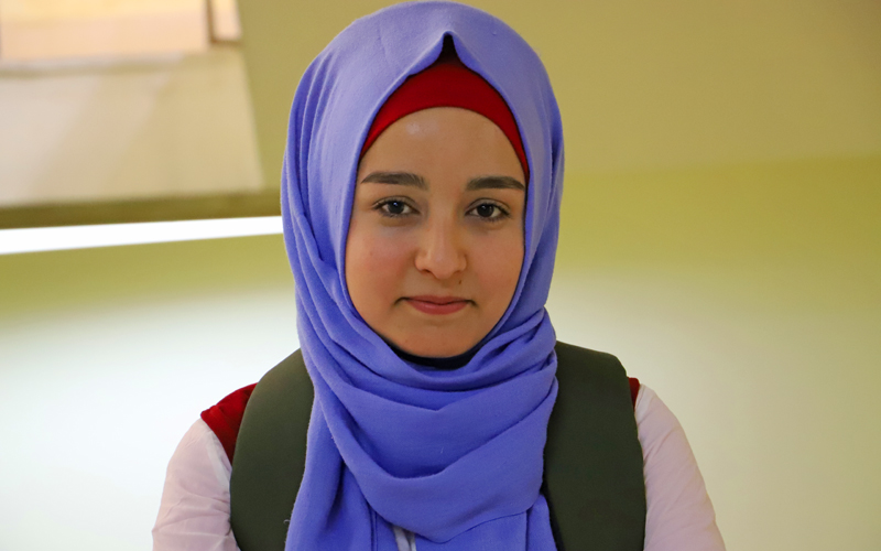 a young woman wearing a head scarf stares straight into the camera.