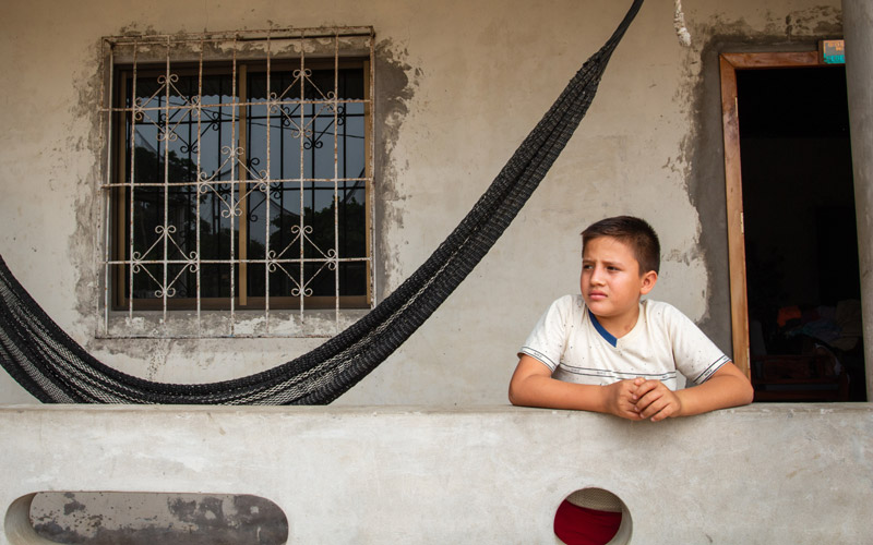 A boy stands besides a hammock in front of a house