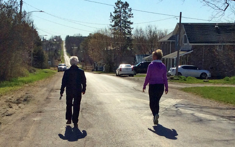 Two Canadian women walking down a country road.