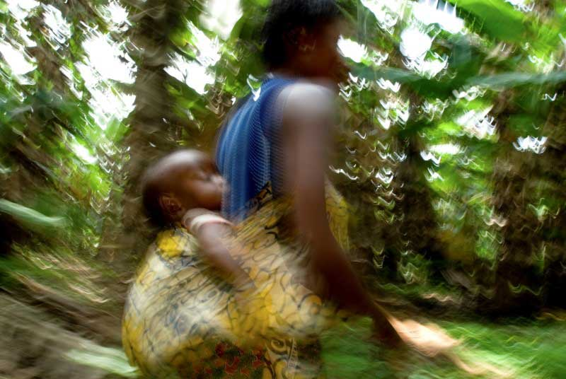A blurry photo of a teen girl carrying her baby on her back in a yellow patterned sling, as she hurries through the jungle.