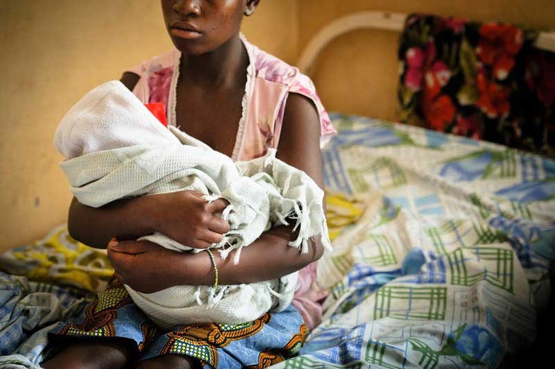 An adolescent girl holds a bundled baby in her arms, while sitting on a hospital bed. We don't see the faces of either.