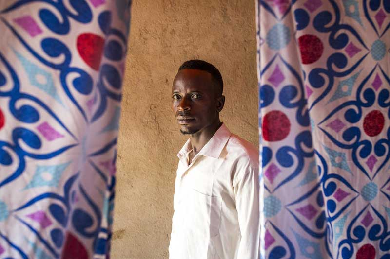 A man from the DRC stands in between colourful curtains.