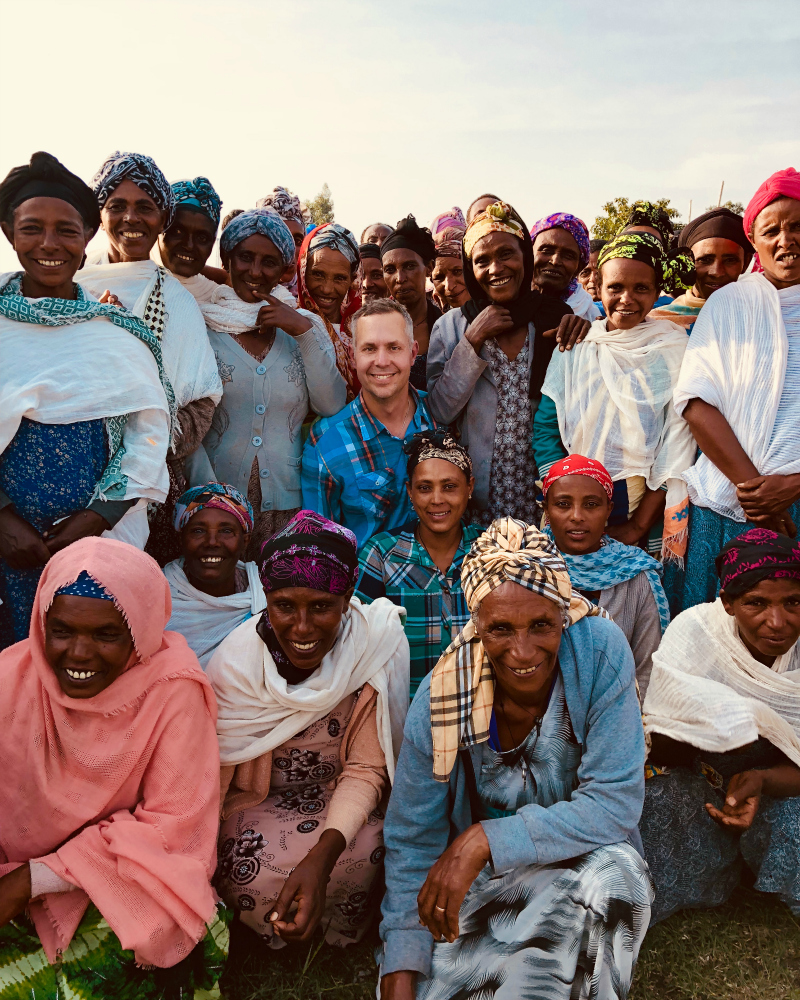 A man stands among a group of smiling Ethiopian women.