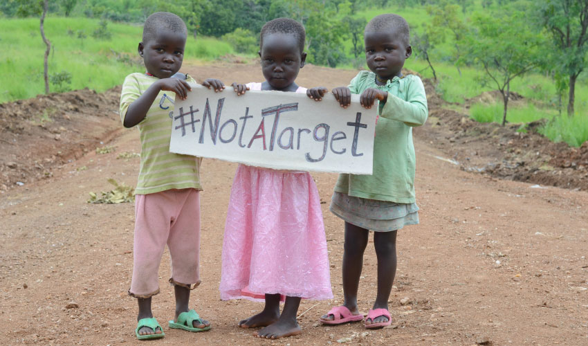 three small children hold a sign that says #NotATarget