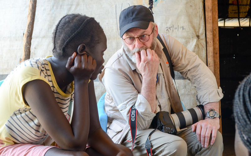 a black woman sits and talks with a white man. He has a beard and holds a large camera