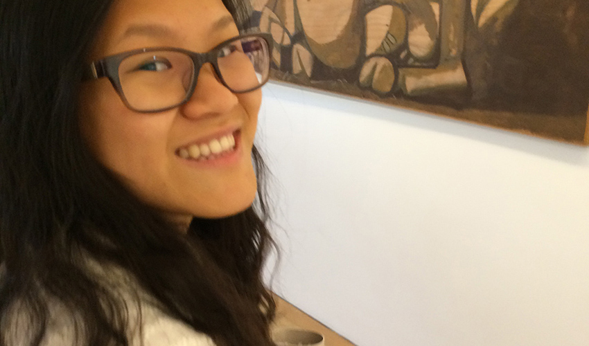 Young woman wearing black framed glasses next to a brown-toned art exhibit.