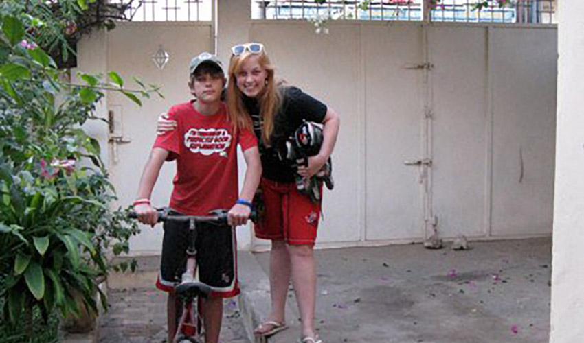 young woman with arm around her little brother who is sitting on bicycle