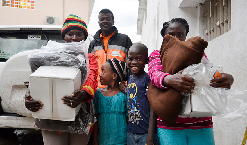 Two women hold bundles beside two smiling children and a man in a World Vision jacket