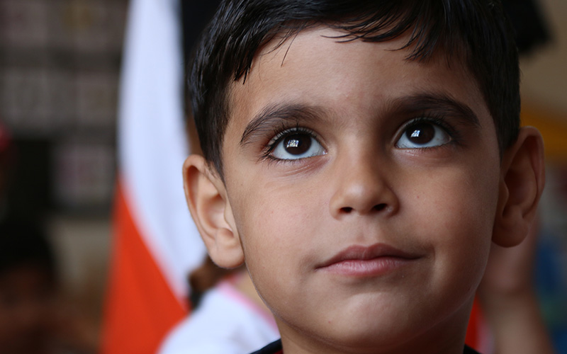 A Syrian refugee child looking up.