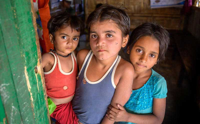 Three young Rohingyan children look into the camera at a World Vision Nutrition Centre located in a refugee camp.