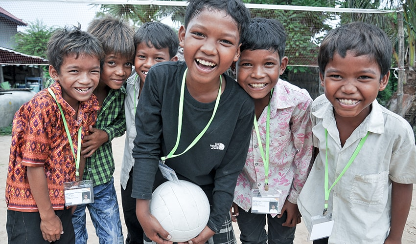 6 Cambodian boys laugh together, while the child in the middle holds a soccer ball.