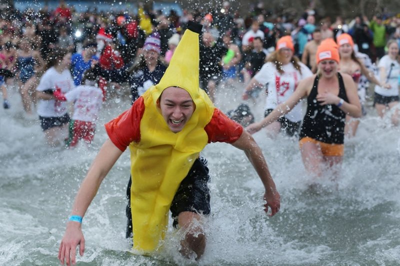 A guy in a banana suit run into a lake while a crowd is behind him.